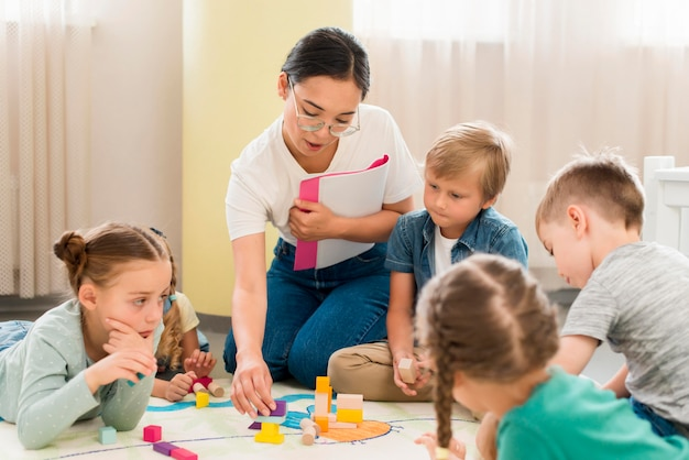 Maestros y niños que tienen una clase en el interior.