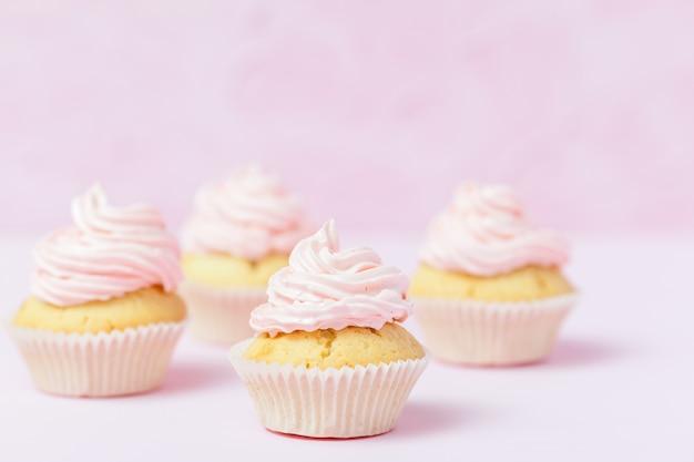 Magdalena adornada con el buttercream rosado en fondo del rosa en colores pastel.