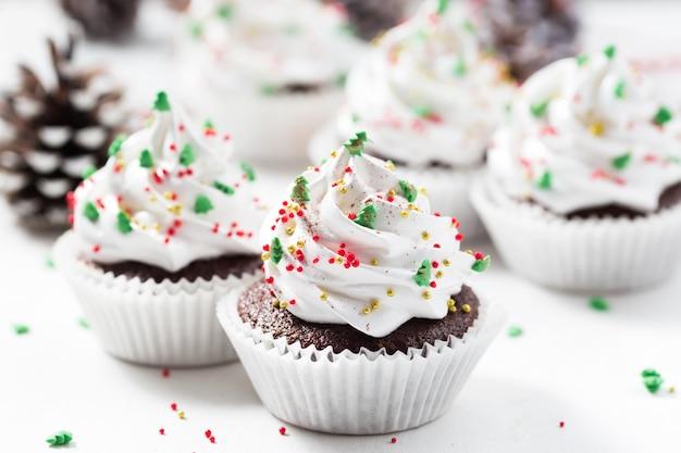Magdalena de chocolate decorado crema blanca y abetos. dulces navideños. postre de año nuevo