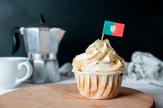 Magdalena de crema de almendras recién horneadas y miga de almendras con la bandera de portugal para la fiesta del té de la mañana