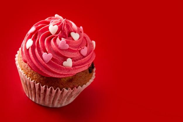 Magdalena decorada con corazones de azúcar para el día de san valentín sobre fondo rojo.