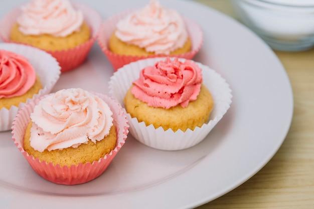 Magdalena fresca con glaseado de mantequilla de rosa en un plato