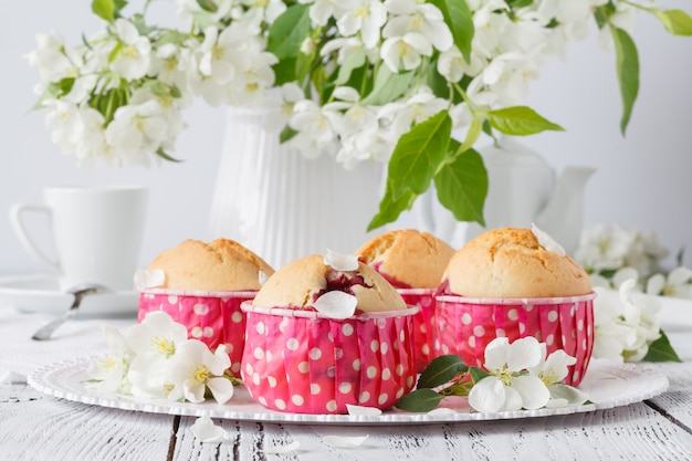 Magdalena o muffin con flor fresca en soporte de magdalenas de papel