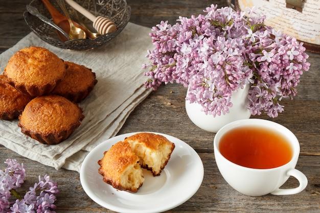 Magdalena en un plato, taza de té, un ramo de lilas, unos muffins. fondo de madera naturaleza muerta.
