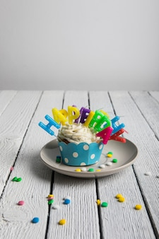 Magdalena con velas de cumpleaños de colores y caramelos en mesa de madera con textura