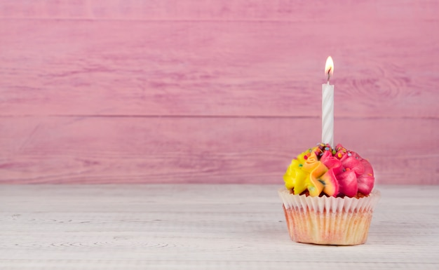 Magdalenas caseras con crema multicolor sobre un fondo rosa copia espacio. crema amarilla y rosa.