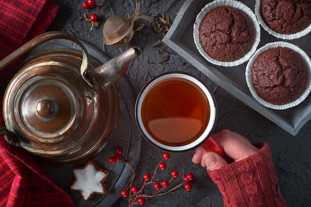 Magdalenas de chocolate, galletas, tetera y decoraciones de invierno