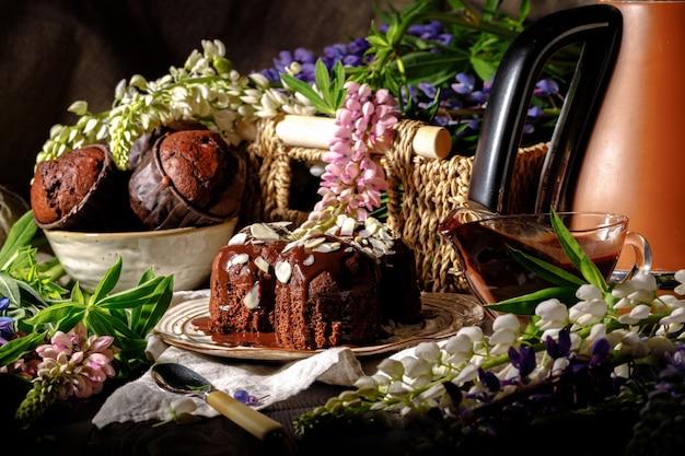 Magdalenas de chocolate con jarabe de chocolate sobre fondo oscuro, enfoque selectivo