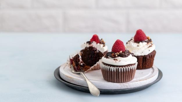 Magdalenas de chocolate con una taza de café y frambuesas frescas sobre la mesa, pancarta ligera,