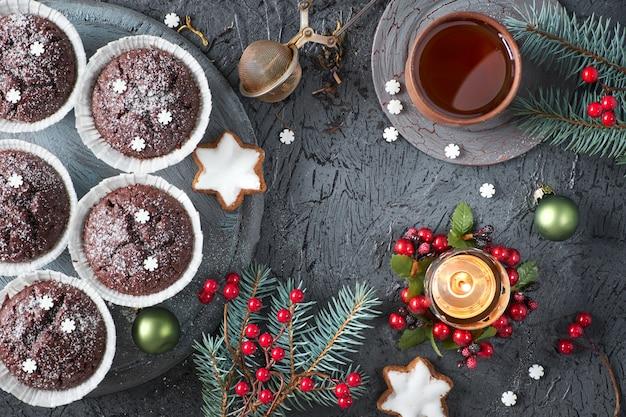 Magdalenas de chocolate, taza de té, malla de té sobre fondo gris rústico con ramas de árbol de navidad decoradas con bayas rojas.