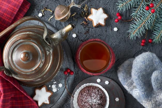 Magdalenas de chocolate, taza de té, malla de té sobre fondo gris rústico con ramas de árbol de navidad decoradas con bayas rojas