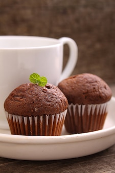 Magdalenas de chocolate con una taza de té en un plato blanco