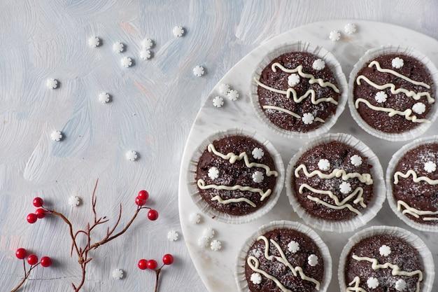 Magdalenas de chocolate en tazas de papel blanco decoradas para navidad