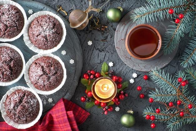 Magdalenas de chocolate y té en madera rústica gris con ramas de árbol de navidad decoradas con bayas rojas