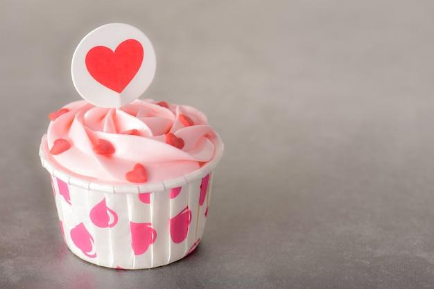 Magdalenas color de rosa sabrosas en colores pastel de la crema de la mantequilla en fondo rojo