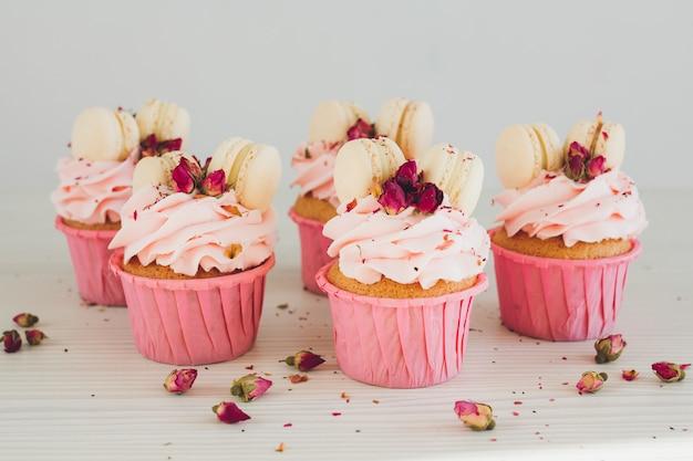 Magdalenas con crema rosa, macarrones y rosas