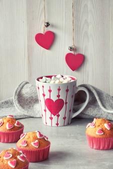 Magdalenas decoradas con corazones de azúcar y una taza con corazón rojo sobre fondo gris claro