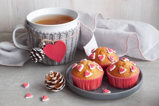 Magdalenas decoradas con corazones de azúcar y una taza con corazón rojo
