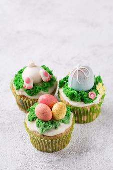Magdalenas festivas con los huevos y la hierba de la masilla en fondo brillante. concepto de vacaciones de semana santa. copia espacio