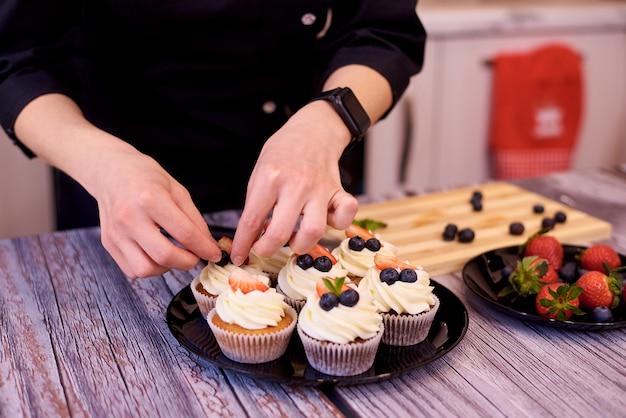 Magdalenas con fresas y arándanos en placa. las manos femeninas llenan los cupcakes en la mesa de la cocina.