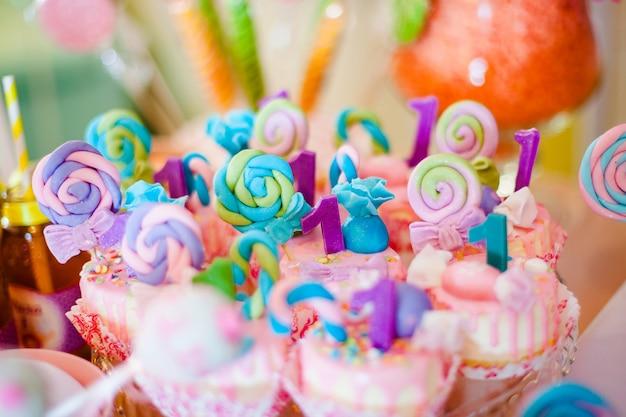 Magdalenas rosas y azules con chupetines de colores para barra de caramelo
