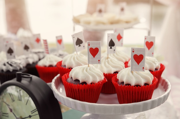Magdalenas de terciopelo rojo con toppers jugando a las cartas, alicia en la fiesta del té del país de las maravillas