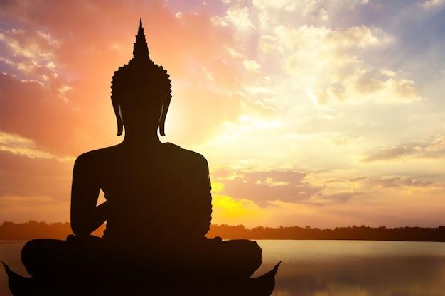 Magha asanha visakha puja day, silueta de buda en la puesta de sol dorada.