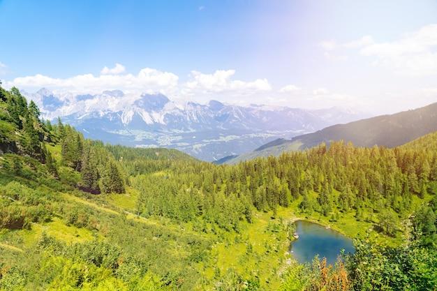 Mágico paisaje idílico con lago en las montañas de los alpes de europa. ruta turística en colinas verdes en los alpes. hermosa roca y admire la increíble vista a los picos de las montañas. fantástico día soleado en el lago de montaña.