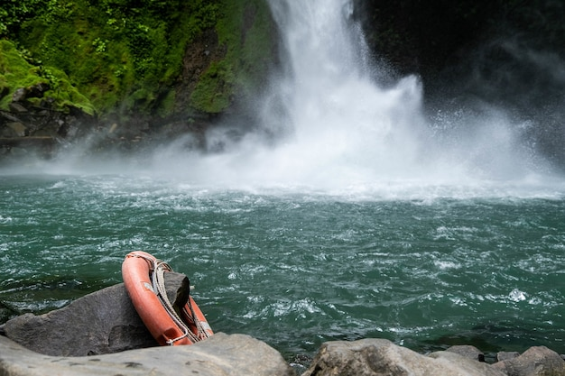 Magnífica cascada y lago rodeado de árboles con un tubo salvavidas que cuelga de una roca
