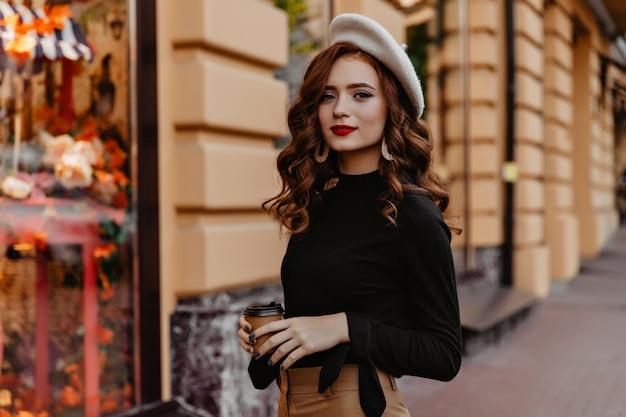 Magnífica chica europea en boina marrón pasar tiempo al aire libre. curiosa dama de jengibre francés de pie en la calle y bebiendo té.