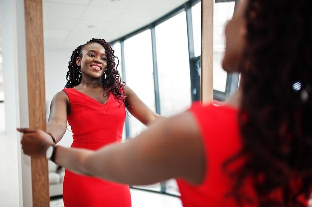 Magnífica joven africana en lujoso vestido rojo en un apartamento de lujo mira en el espejo. belleza, moda.