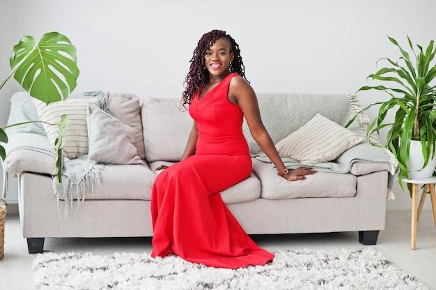 Magnífica joven africana en lujoso vestido rojo en un apartamento de lujo sentado en el sofá. belleza, moda.