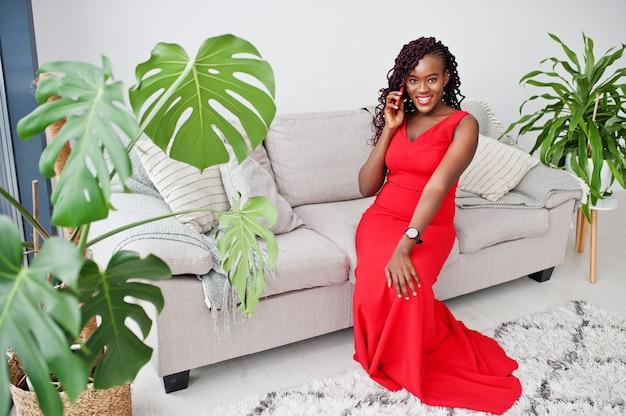 Magnífica joven africana en lujoso vestido rojo en un apartamento de lujo sentado en el sofá con teléfono móvil. belleza, moda.