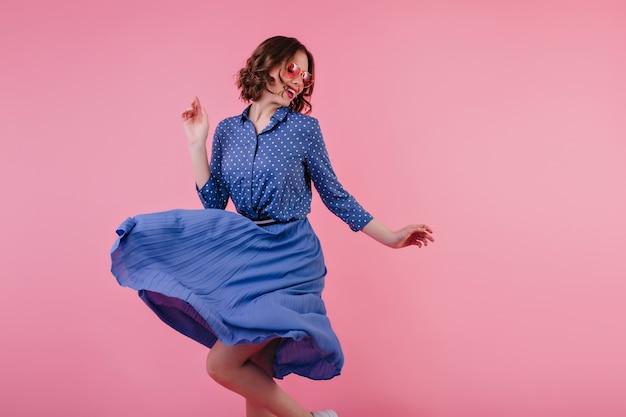 Magnífica modelo femenina en falda midi bailando y riendo en la pared rosa. mujer caucásica emocionada en ropa azul que expresa emociones positivas.