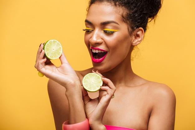 Magnífica mujer afroamericana con maquillaje de moda sosteniendo dos mitades de limón fresco en ambas manos aisladas, sobre pared amarilla