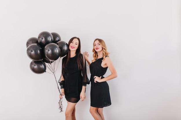 Magníficas mujeres morenas de pie con globos negros en estudio