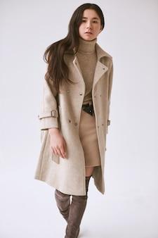 Magnífico retrato de mujer asiática elegante en abrigo de lana de moda y falda clásica aislado en blanco