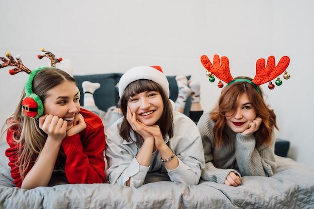 Magníficos amigos sonrientes divirtiéndose y disfrutando de la fiesta de pijamas