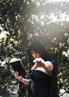 Mago femenino practicando brujería en el bosque iluminado por el sol