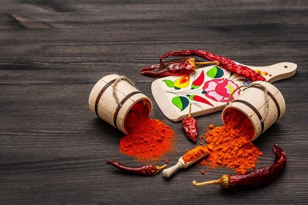 Magyar (húngaro) pimentón rojo dulce y caliente en polvo. patrón tradicional en una tabla de cortar, diferentes variedades de pimiento seco.