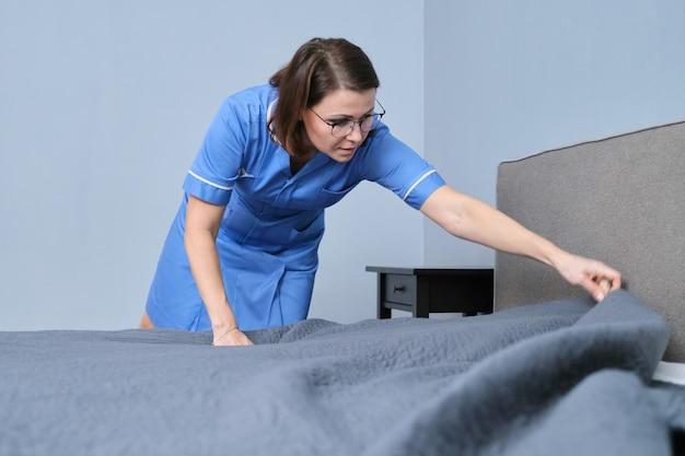 Maid profesional femenino de mediana edad haciendo la cama en la habitación del hotel