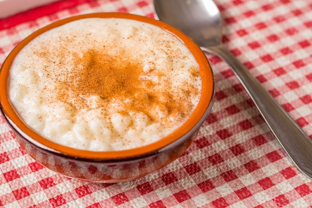 Maíz blanco cocinado con leche conocida como canjica o mungunza, en un recipiente rústico en la mesa de madera. plato típico del partido brasileño llamado festa junina.
