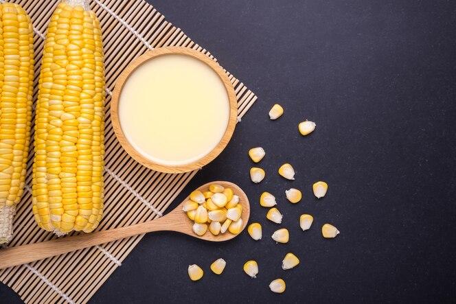 Maíz dulce amarillo en la mazorca y jugo de maíz