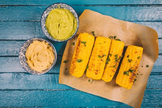 Maíz dulce orgánico asado con guacamole y salsa en la mesa de madera azul