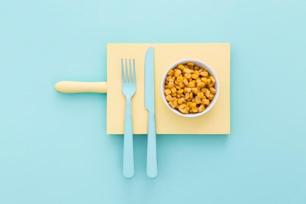 Maíz orgánico y cubiertos en la mesa
