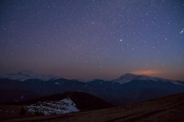 Majestuosa vista del fantástico cielo estrellado y oscuro sobre las magníficas montañas de los cárpatos cubiertas de bosques de hoja perenne y picos nevados en la distancia. impresionante panorama de la belleza y la magia de la naturaleza.
