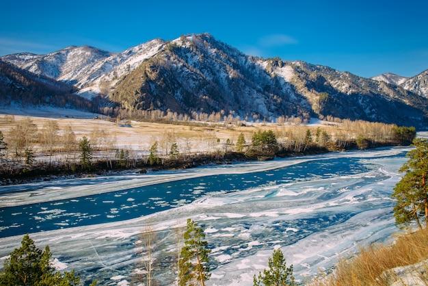 Majestuosa vista panorámica del valle cubierto de nieve, río turquesa en el fondo de montañas nevadas y cielo azul claro. día soleado de invierno en las montañas.