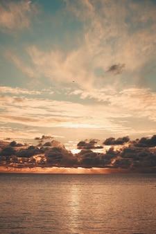 Majestuosas llamaradas de sol que atraviesan las nubes durante una puesta de sol sobre el océano en tonos naranja y con espacio de copia