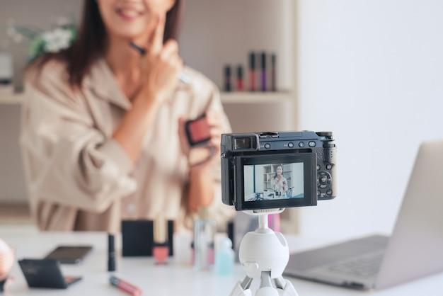 Makeup beauty blogger de moda que graba un video que presenta cosméticos de maquillaje en el hogar influenciador en concepto de redes sociales.