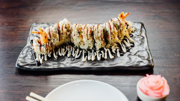 Maki sushi con arroz, tempura de camarones, aguacate y queso dentro de harina de tempura crujiente cubierta. cubriendo con salsa teriyaki y mayonesa.